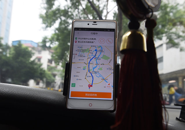 A taxi driver uses the Didi Chuxing app while driving along a street in Guilin