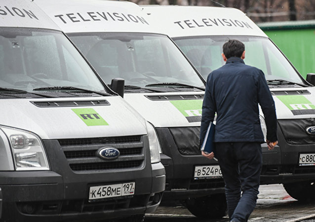 Автомобили телеканала Russia Today возле офиса компании в Москве