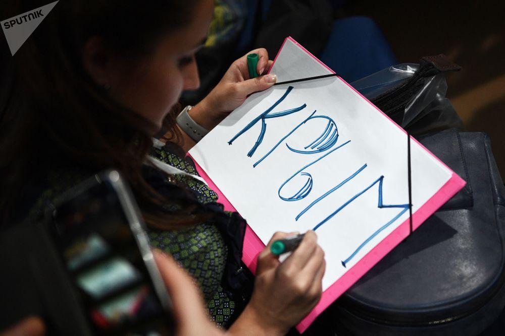 一名女记者正在准备招贴画,希望借此吸引总统的注意。