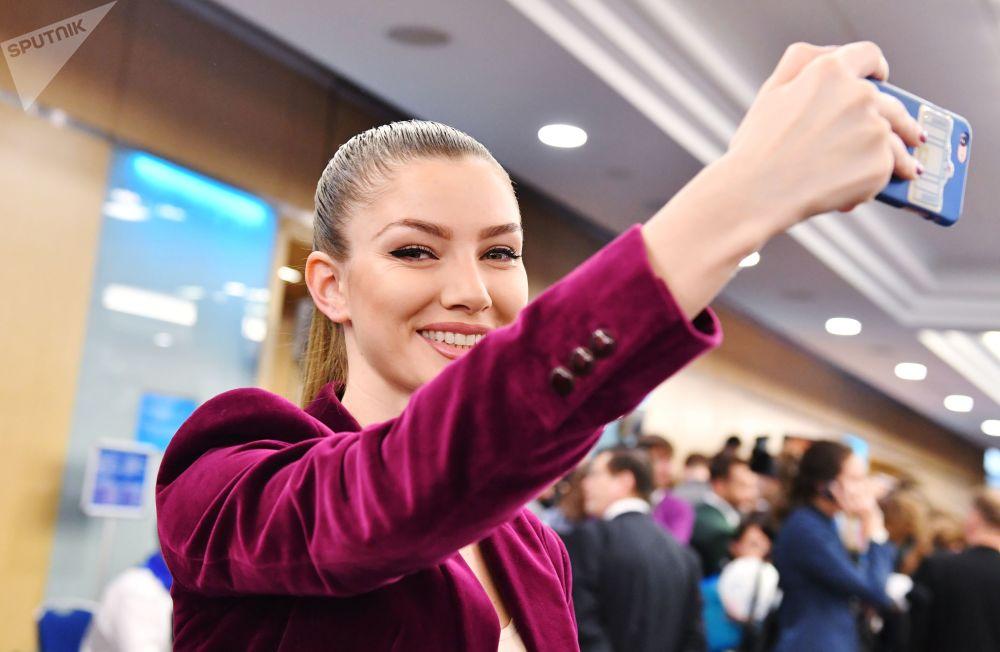 一名女记者在普京大型记者会开始前拍照。