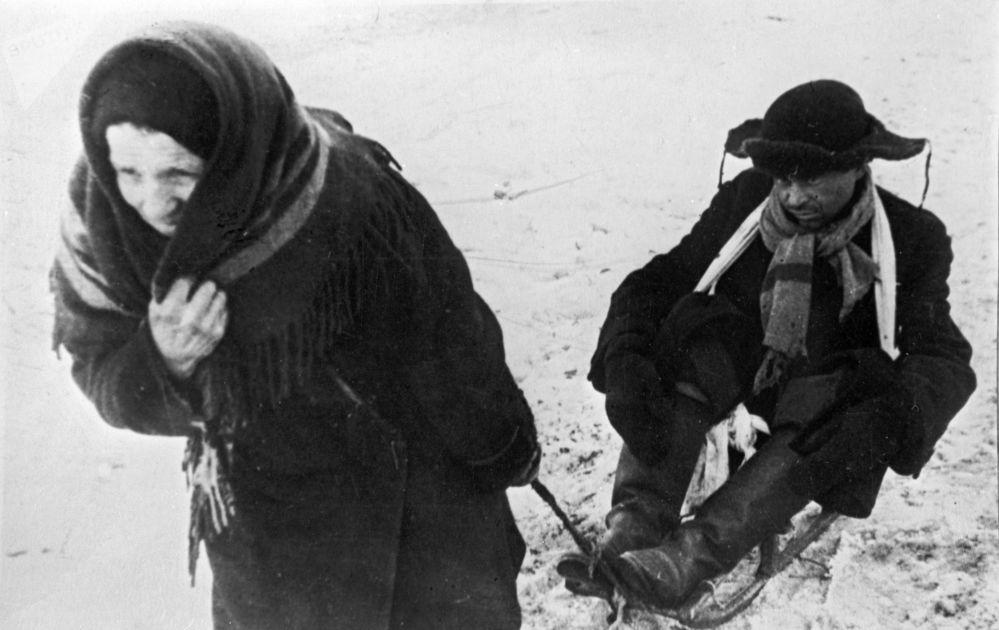 女子用雪橇拉着饥饿的丈夫