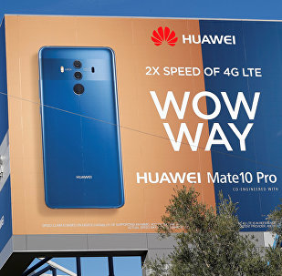 A crew hangs a Huawei advertising banner on the side of the Las Vegas Convention Center