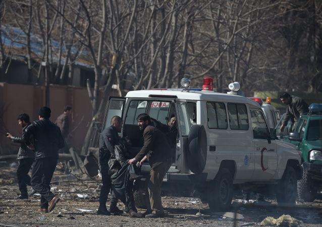 志愿者和警察们正在将在喀布尔爆炸的伤者移送到救护车中