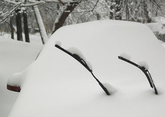 一名美国父亲用自己的孩子清扫车上的积雪