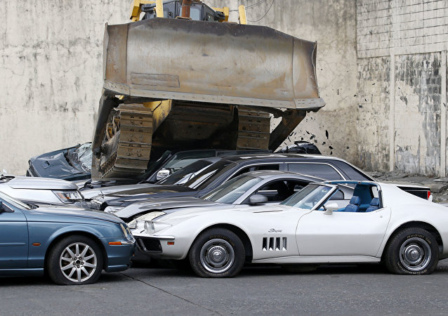 A bulldozer runs over a fleet of used luxury and sports cars during condemnation ceremony as part of the 116th anniversary celebration of the Bureau of Customs in Manila, Philippines