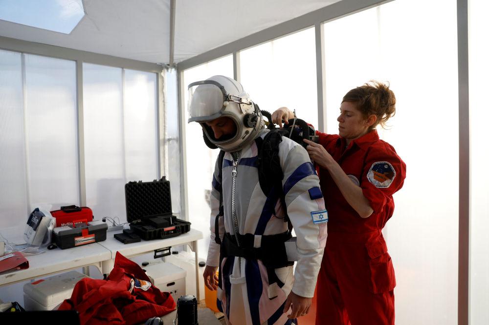 """他们将生活在由太能能电池供电的紧凑舱内,开展科学试验,通过卫星与控制中心保持联络,身着密闭飞行服""""来到地球表面""""。"""