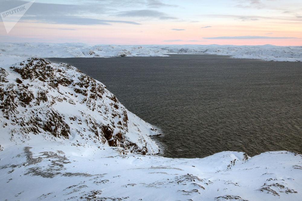 籠罩在摩爾曼斯克州科拉半島捷里別爾斯卡婭灣石質海岸的冬日陽光