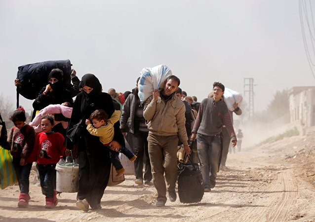 People walk with their belongings as they flee the rebel-held town of Hammouriyeh, in the village of Beit Sawa, eastern Ghouta, Syria