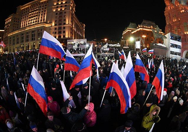 Участники перед началом митинг-концерта на Манежной площади в Москве, посвященного годовщине воссоединения Крыма с Россией
