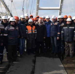 俄羅斯總統弗拉基米爾·普京視察克里米亞已建成通車段時與工人在一起。