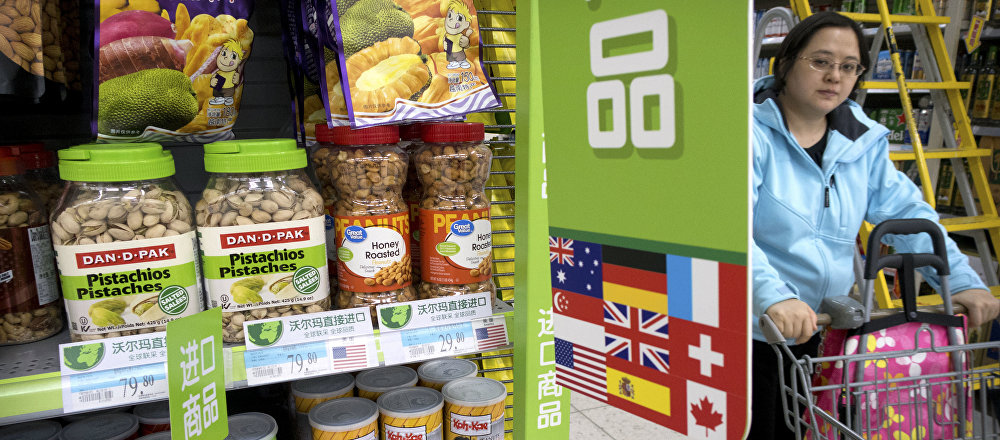 A woman pushes a shopping cart past a display of nuts imported from the United States at a supermarket in Beijing