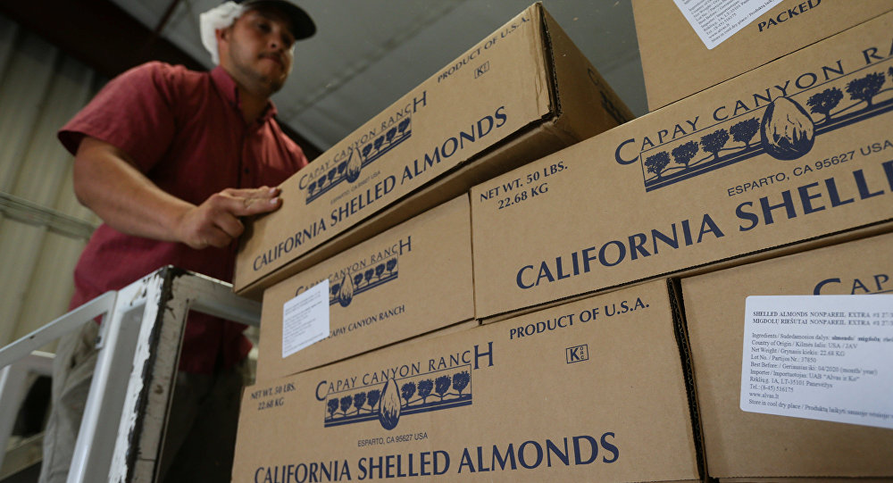 A man stacks boxes of almonds for shipping at Capay Canyon Ranch in Esparto, California