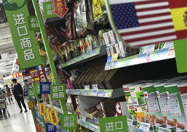 Women push a shopping cart near nuts and sweets imported from the United States and other countries displayed on a section selling imported foods at a supermarket in Beijing