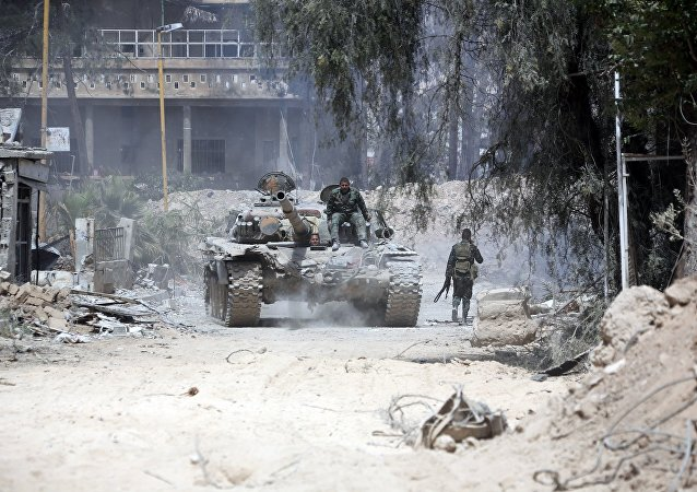 Syrian Army soldiers advancing in an area on the eastern outskirts of Douma