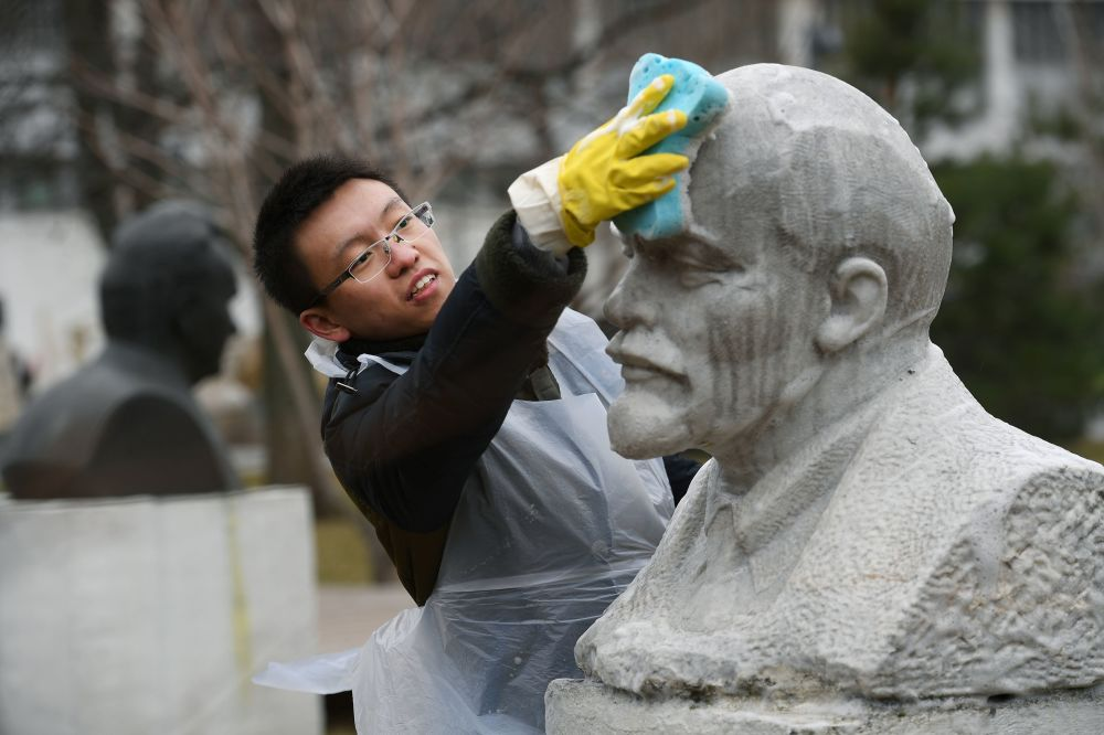 一名志願者在清洗列寧雕像。