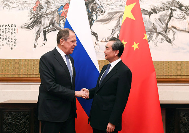 Russian Foreign Minister Sergei Lavrov shakes hands with Chinese State Councilor and Foreign Minister Wang Yi at the Diaoyutai State Guest House in Beijing