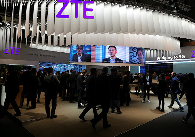 People stand at ZTE's booth during Mobile World Congress in Barcelona