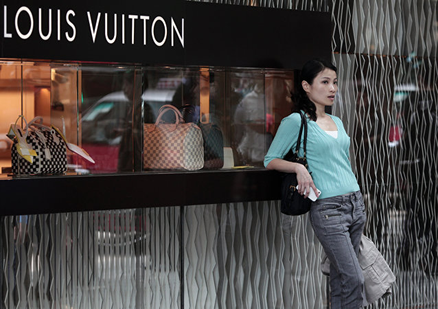 A Chinese woman leaning on a Louis Vuitton shop display window
