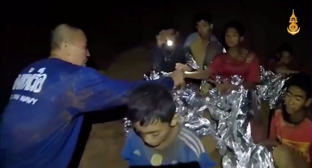 Boys from the under-16 soccer team trapped inside Tham Luang cave receive treatment from a medic in Chiang Rai, Thailand
