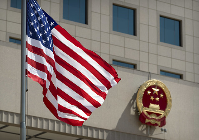 The American flag flies near the national emblem of China outside of the Bayi Building