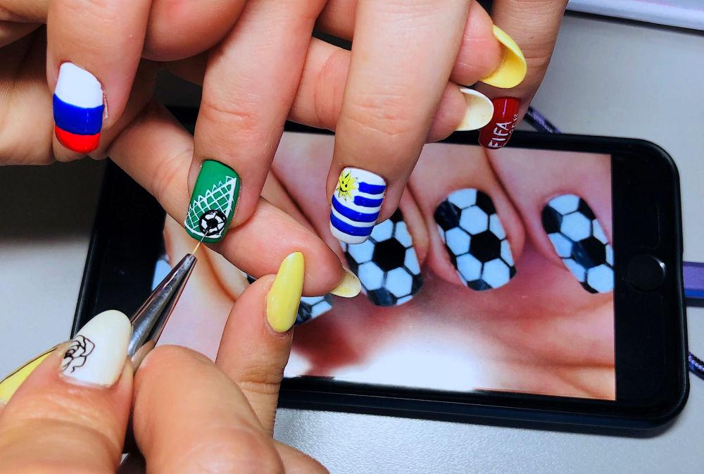 俄罗斯姑娘用世界杯参赛国家的国旗作为图案做美甲。