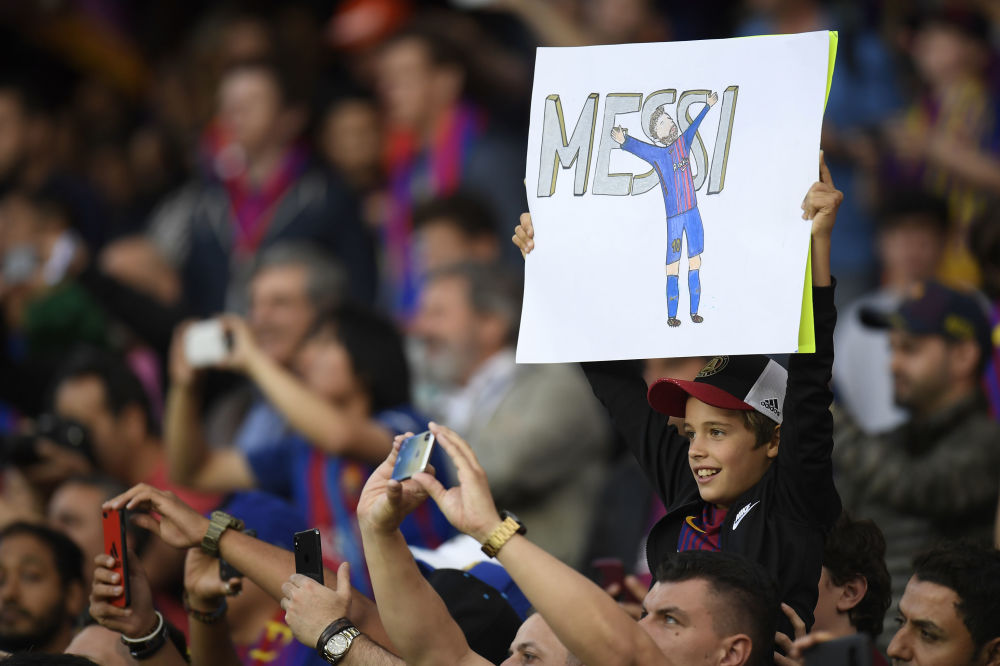 巴塞罗那。在巴塞罗那队和皇家马德里队比赛前,拿着印有巴塞罗那队前锋梅西肖像的海报的小球迷。