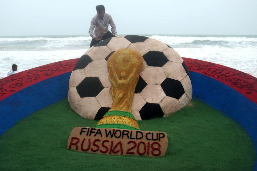 """艺术家苏达尔尚·帕特纳伊克在印度""""普里""""海滩上对和俄罗斯世界杯足球赛有关的沙雕进行最新调整。"""