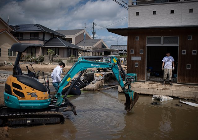 People remove water and mud with an excavator in a flood hit area in Mabi, Okayama prefecture