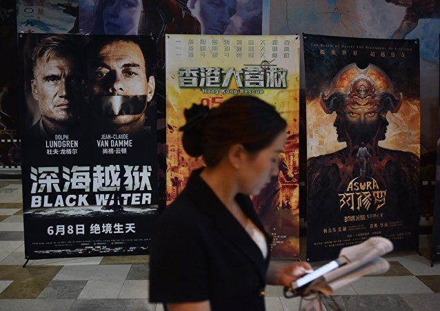 A woman looks at her mobile phone near movie posters outside a theater in Beijing