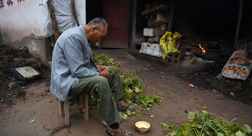 A man preparing beans outside his house at a village