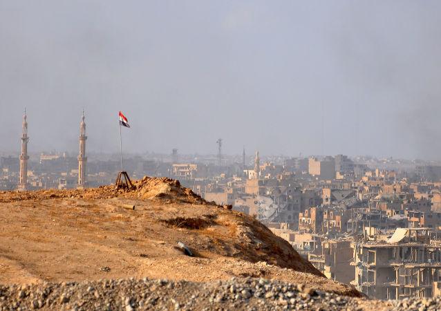 Сирийский флаг на фоне города Дейр-эз-Зор
