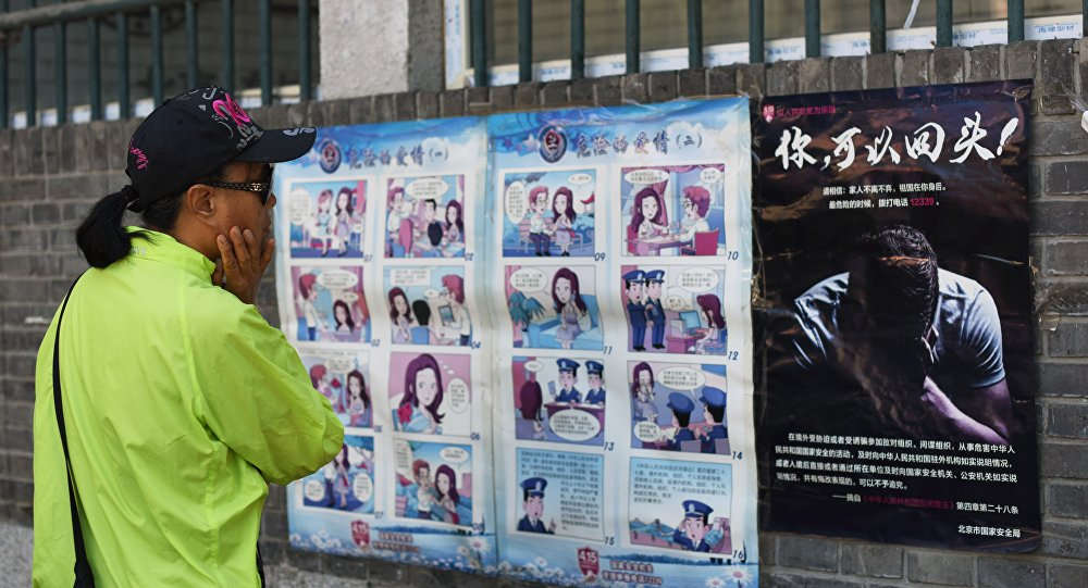 A woman looks at a propaganda cartoon warning local residents about foreign spies, in an alley in Beijing