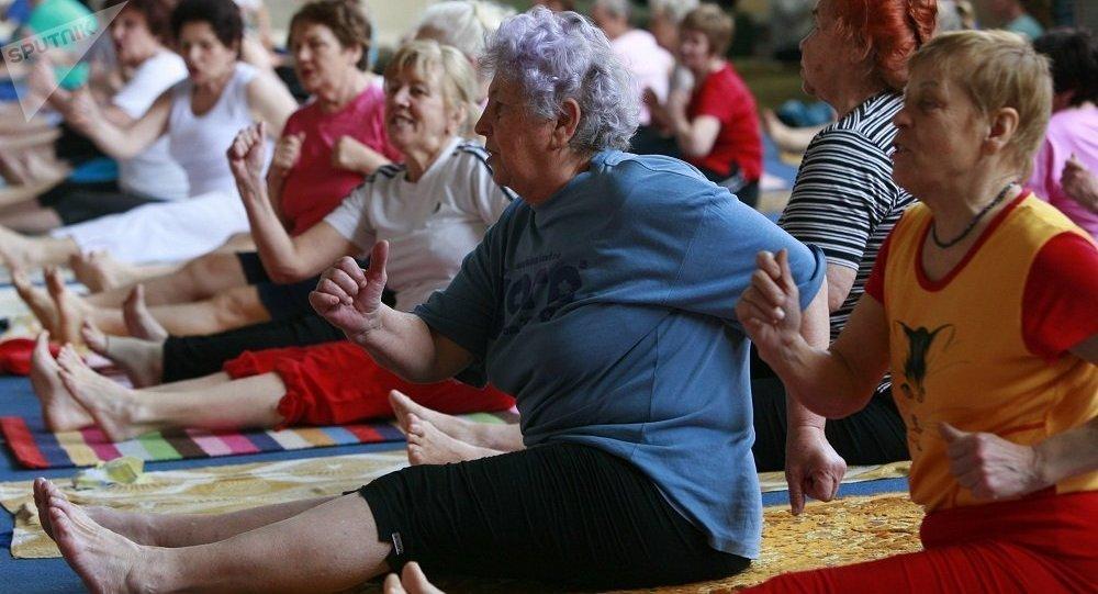 上年纪的妇女在健身房练诃陀瑜伽