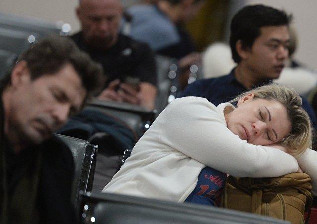 Пассажиры в аэропорту спят.