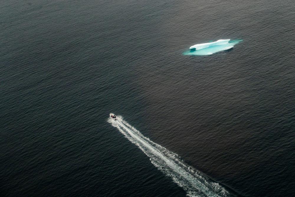 一艘小艇驶过塔西拉克镇旁的开阔海域上的冰山,格陵兰岛