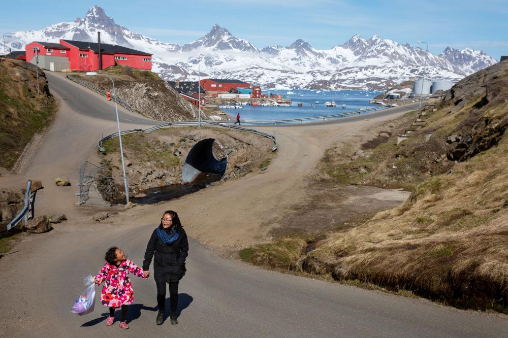 女人和孩子沿着塔西拉克镇的街道散步,格陵兰岛