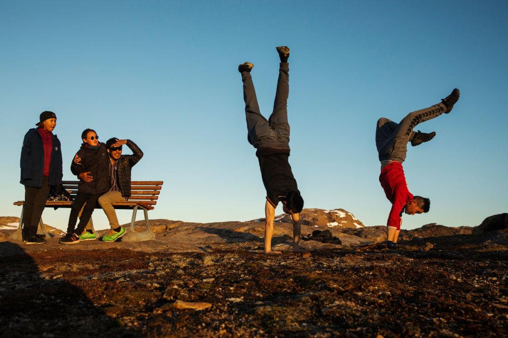 年轻人在塔西拉克镇外的小山上玩耍,格陵兰岛
