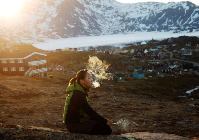 年轻的女孩坐在石头上,在落日的余晖中抽烟,塔西拉克镇(Tasiilaq Town),格陵兰岛