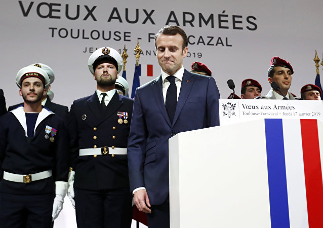 French President Emmanuel Macron (C) reacts as he delivers his 2019 New Year's wishes to the military forces at the air force base 101 Toulouse-Francazal.