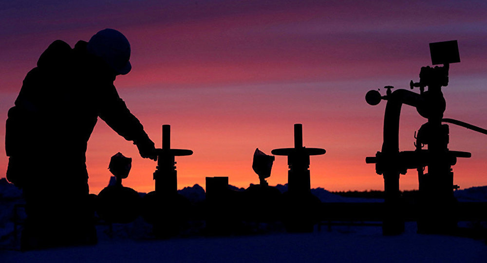 A worker checks the valve of an oil pipe at an oil field