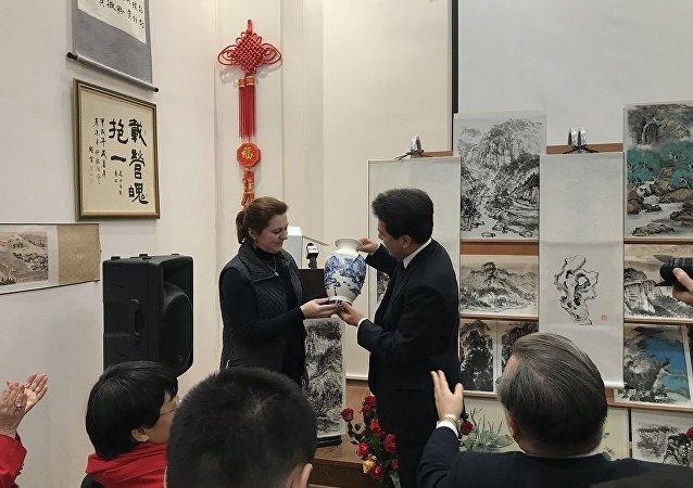 由俄罗斯女画家安娜∙多琴科把自己绘制的瓷器赠给出席展览会的中国驻俄罗斯大使
