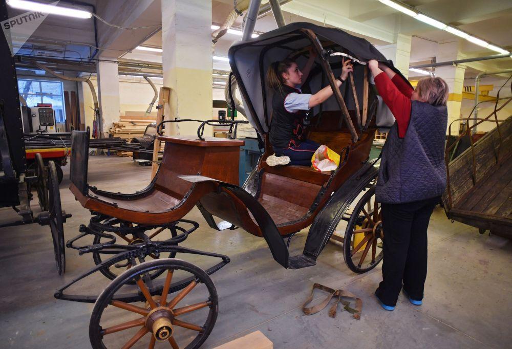 员工正在莫斯科电影制片厂道具间装饰轿式马车车厢