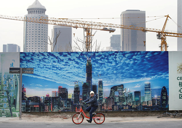A man cycles outside construction sites in Beijing