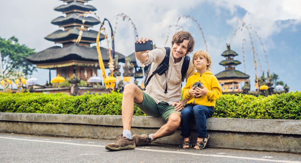 Туристы фотографируются у храма Улун Даноу на Бали