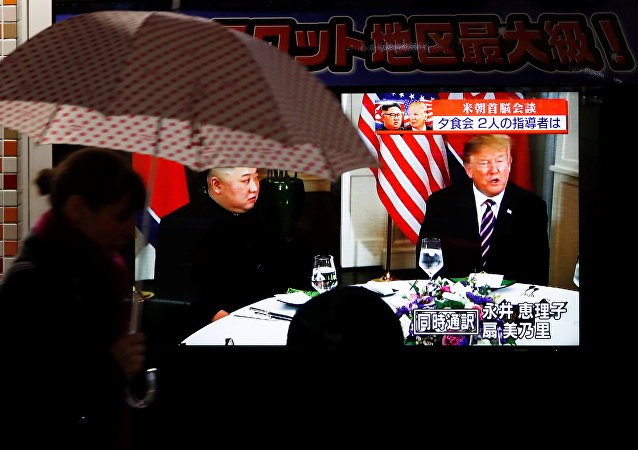 A passerby walks past a screen broadcasting a meeting between U.S. President Donald Trump and North Korean leader Kim Jong Un at their second U.S.-North Korea summit, in Tokyo