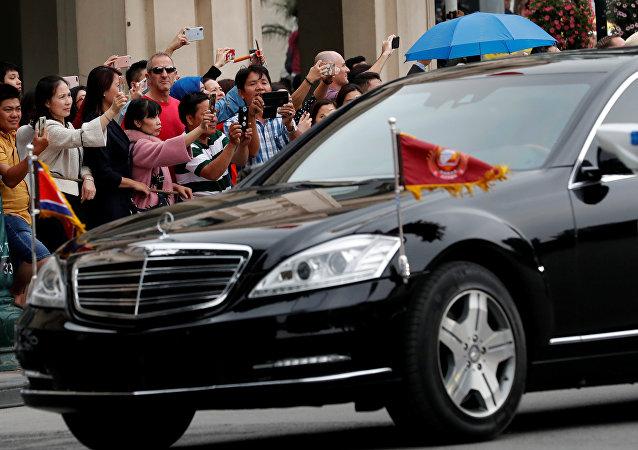 Bystanders take photos of North Korean leader Kim Jong Un's motorcade as it leaves the Metropole after the North Korea-U.S. summit in Hanoi