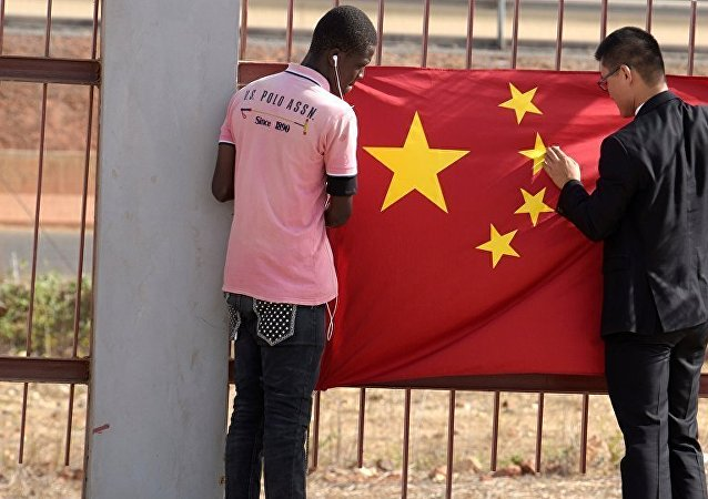 A Senegalese worker and a Chinese man put a Chinese flag in Diamniadio district in Dakar