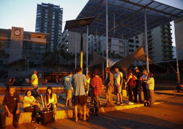 Люди выстроились в очередь к аккумулятору с солнечной панелью на площади в Каракасе