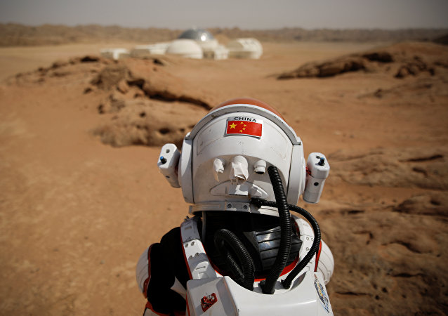 A staff member wearing a mock space suit poses in the Gobi Desert near the C-Space Project Mars simulation base outside Jinchang