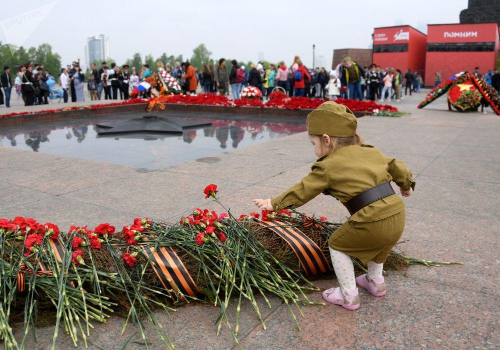 小女孩在胜利日庆祝活动中向莫斯科俯首山上的长明火献花